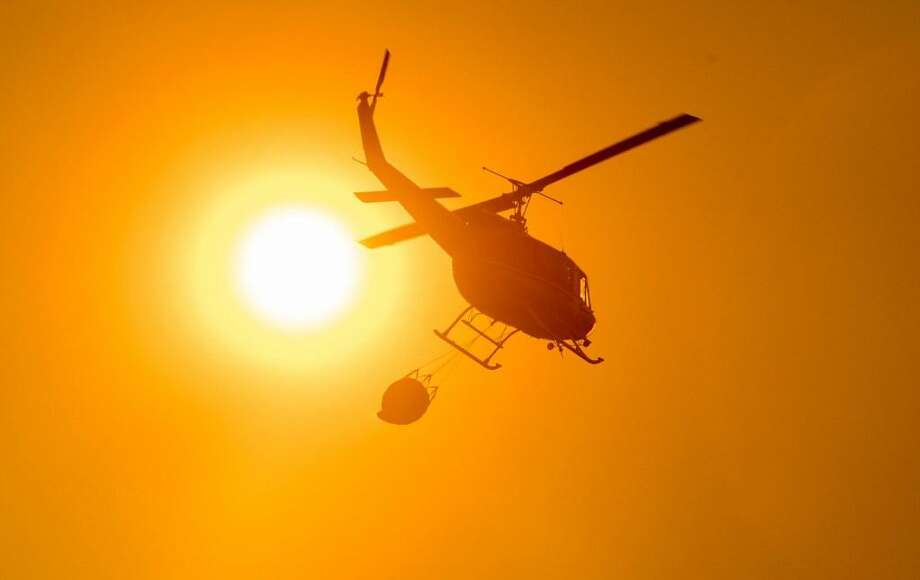A helicopter carries water to a drop point over the Detwiler Fire in Mariposa on July 19. The fire continues to smolder as high temperatures return this week to the Central Valley and Bay Area. Photo: Josh Edelson / AFP / Getty Images / Josh Edelson / AFP / Getty Images
