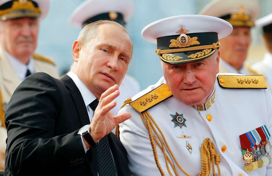 Russian President Vladimir Putin talks with Navy Admiral Vladimir Korolev at a military parade in Saint Petersburg. The diplomatic expulsions are in retaliation for U.S. sanctions. Photo: ALEXANDER ZEMLIANICHENKO, AFP/Getty Images