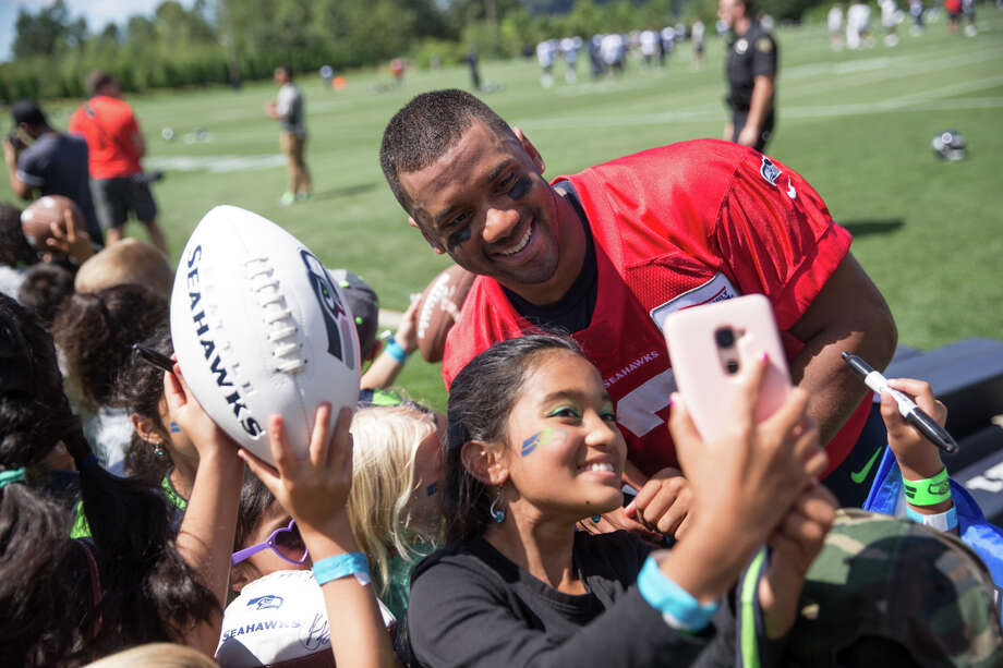 Quarterback Russell Wilson poses for a selfie with a young fan following the first day of practice on Sunday, July 30, 2017. Photo: GRANT HINDSLEY, SEATTLEPI.COM / SEATTLEPI.COM