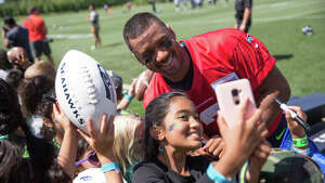 Quarterback Russell Wilson poses for a selfie with a young fan following the first day of practice on Sunday, July 30, 2017.