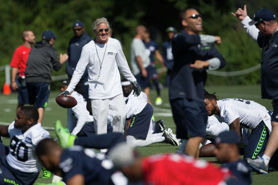 Head coach Pete Carroll visits with his team as they stretch during the first day of practice on Sunday, July 30, 2017. Photo: GRANT HINDSLEY, SEATTLEPI.COM / SEATTLEPI.COM