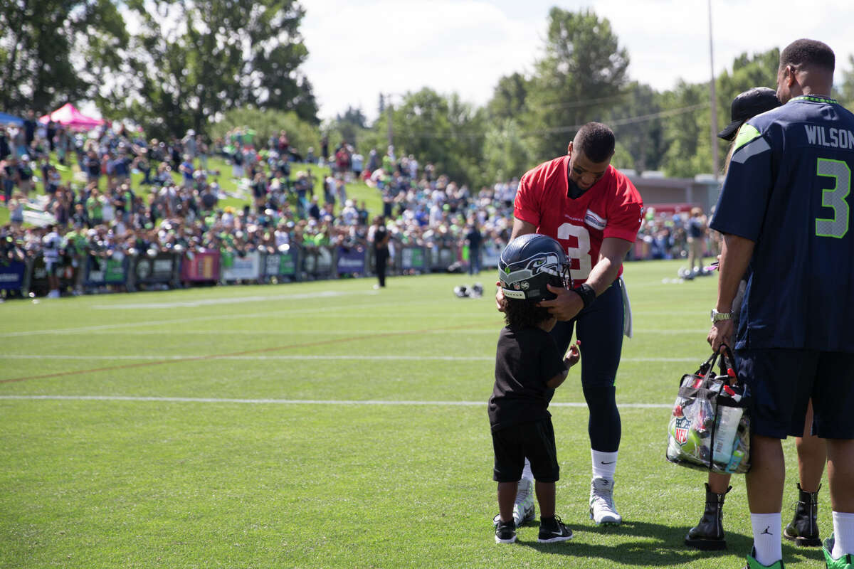 Quarterback Russell Wilson puts his helmet on his stepson, Future Zahir's, head following the first day of practice on Sunday, July 30, 2017.
