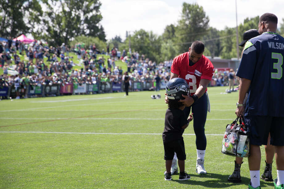 Quarterback Russell Wilson puts his helmet on his stepson, Future Zahir's, head following the first day of practice on Sunday, July 30, 2017. Photo: GRANT HINDSLEY, SEATTLEPI.COM / SEATTLEPI.COM