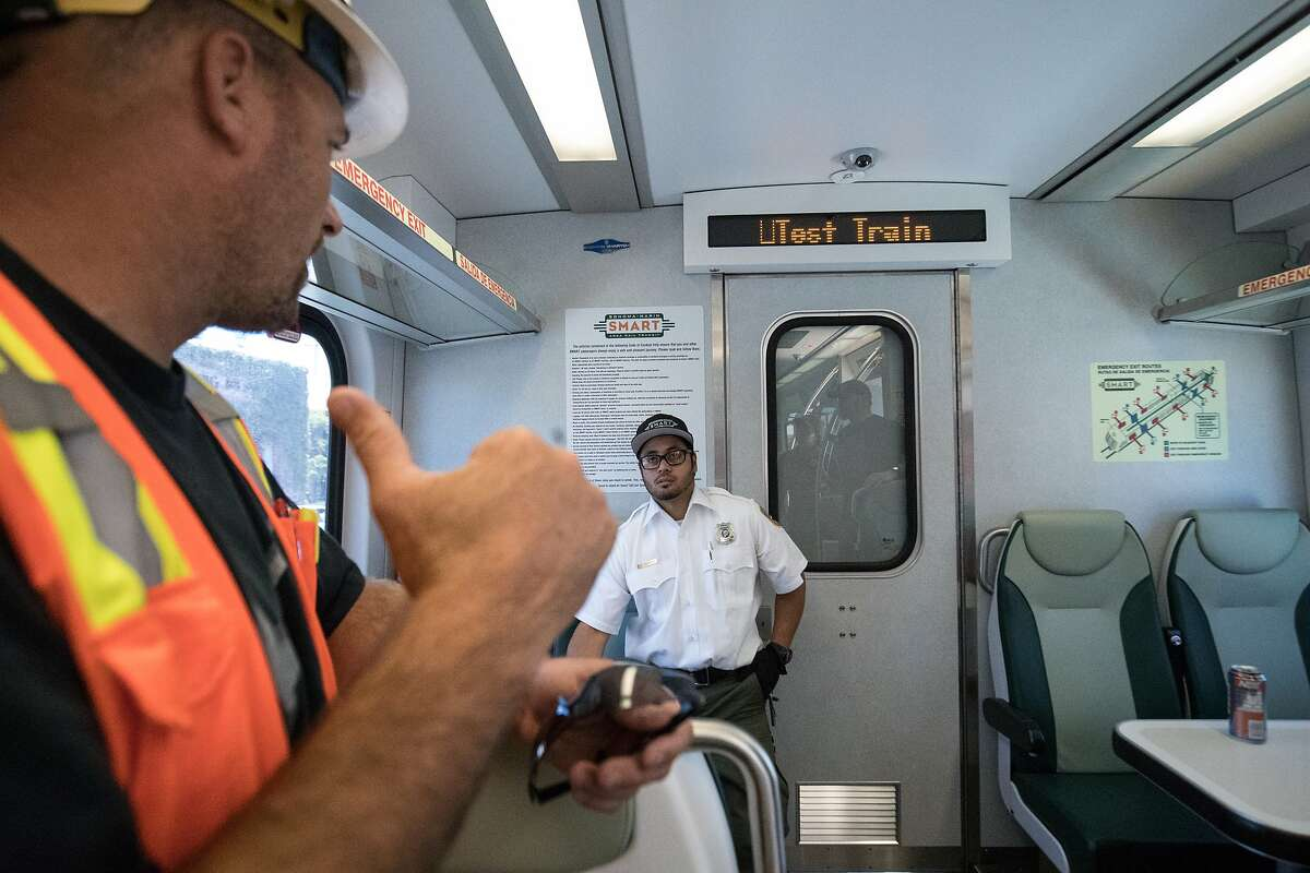 Colby Phillips, test engineer, meets with Josh Sturgeon, conductor engineer, during a stop of a testing Smart train at the Petaluma train station on Sunday, July 30, 2017 in Petaluma, CA.