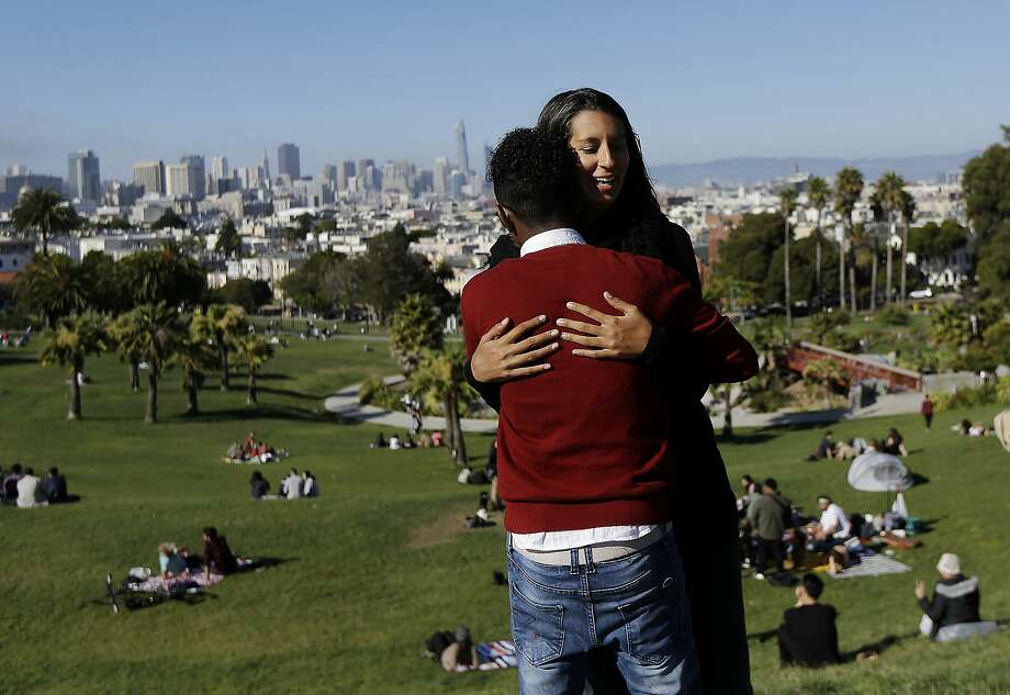 In this July 14, 2017 photo, Julie Rajagopal, facing, hugs her 16-year-old foster child from Eritrea after posing for photos at Dolores Park in San Francisco. When he landed in March, he was among the last refugee foster children to make it into the U.S. Trump administration travel bans declared to block terrorists also are halting a small, three-decade-old program bringing orphan refugee children to waiting foster families in the United States. (AP Photo/Jeff Chiu) Photo: Jeff Chiu, Associated Press
