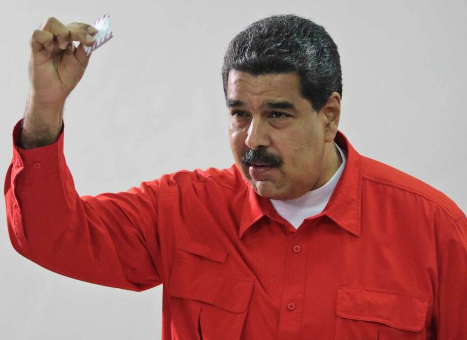 In this photo released by Miraflores Press Office, Venezuela's President Nicolas Maduro shows his ballot after casting a vote for a constitutional assembly in Caracas, Venezuela on Sunday, July 30, 2017. Maduro asked for global acceptance on Sunday as he cast an unusual pre-dawn vote for an all-powerful constitutional assembly that his opponents fear he'll use to replace Venezuelan democracy with a single-party authoritarian system. (Miraflores Press Office via AP) Photo: HOGP / Miraflores Press Office