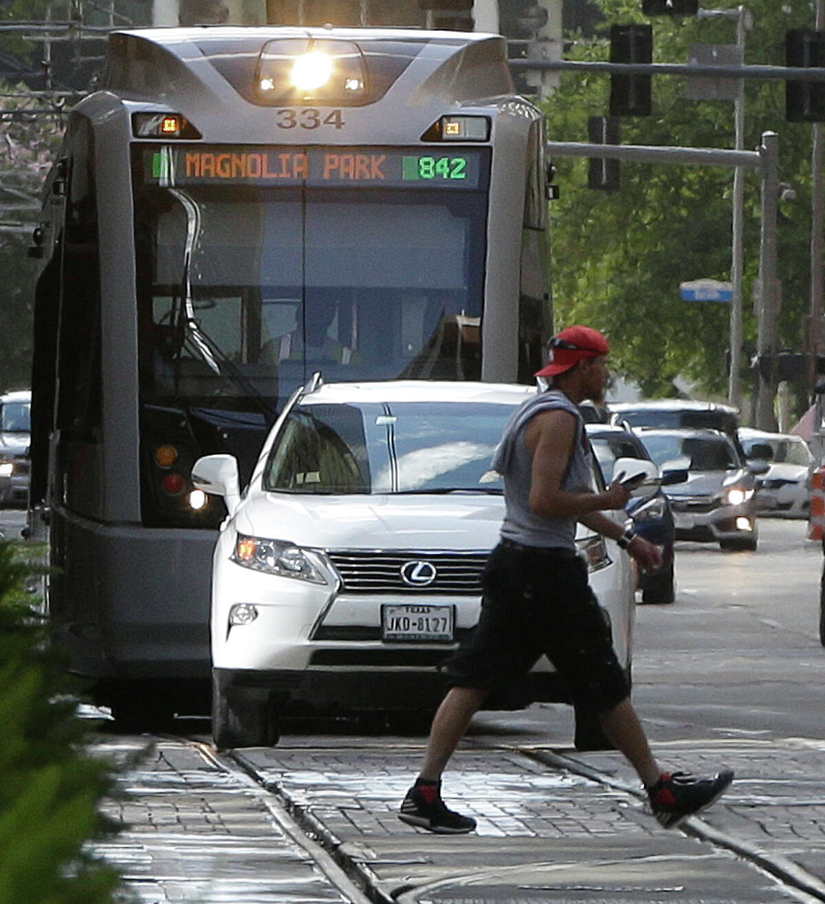 A Metro light rail train sits behind a car waiting to turn from Rusk onto Main.