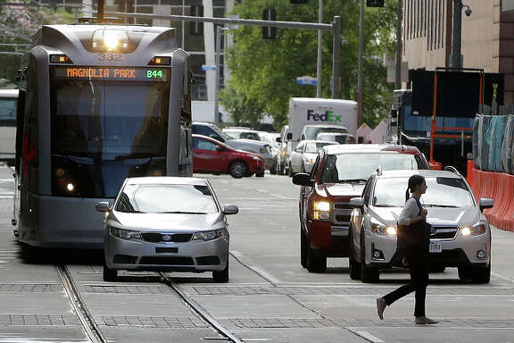 A Metro light rail train sits behind a car on Rusk near Fannin Wednesday.