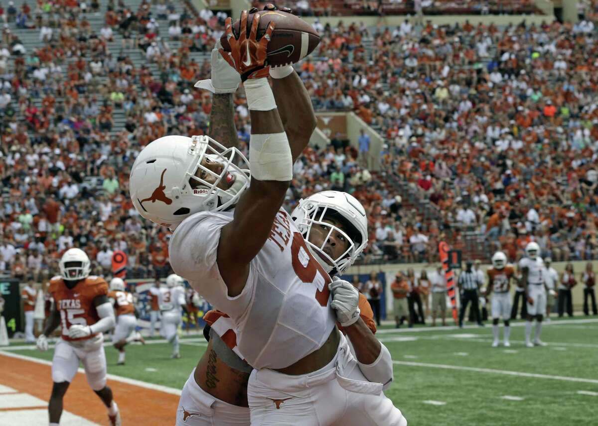 Collin Johnson snares a touchdown pass thrown by Shane Buechele over the defense of Eric Cuffee as the Texas Longhorns play their Orange-White spring game on April 15, 2017.