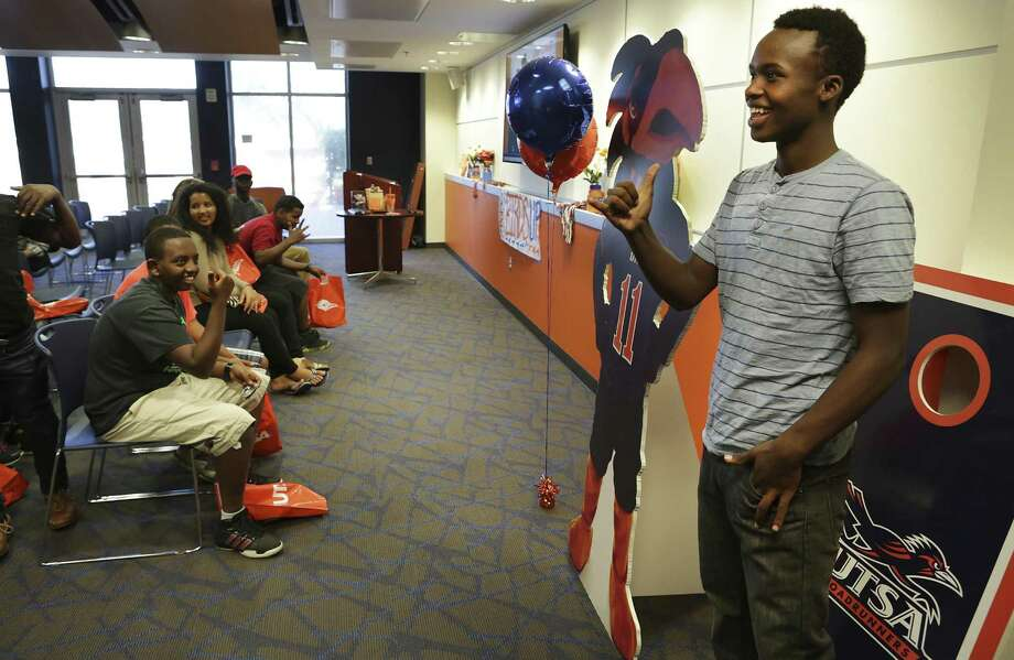 "Freddy Muhumure, right, 17, of Rwanda, shows the UTSA hand sign as he has his picture taken with a poster of ""Rowdy"", the school's mascot.  Seth and Angela Sampson, who are school counselors, partnered with the Center for Refugee Services, to form Camp Discover which helps refugee high school students prepare for college.  On Monday, July 10, 2017 a dozen students toured the UTSA campus. Photo: Bob Owen, Staff / San Antonio Express-News / ©2017 San Antonio Express-News"