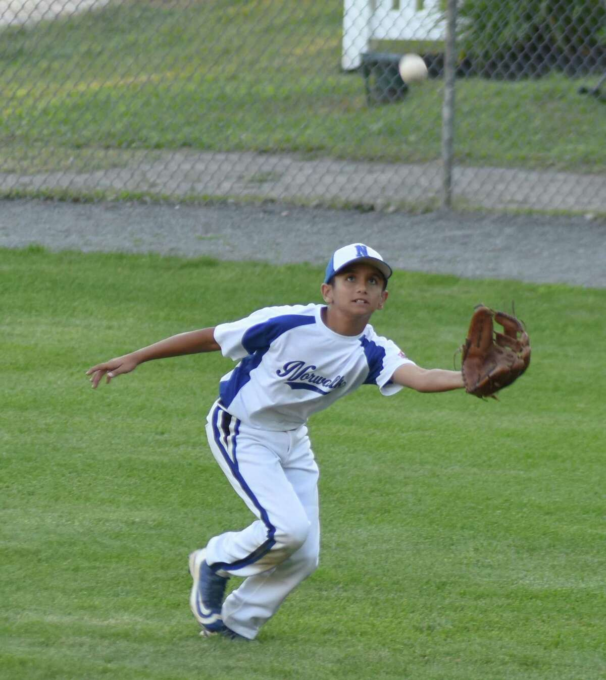 Norwalk's Taso Panagiotidis tracks down a fly ball in right field during Sunday's Cal Ripken Baseball 11-year-old New England Tournament game against Hudson, Mass., at Beckwith Park in Dover, N.H. Norwalk won the game 12-2.