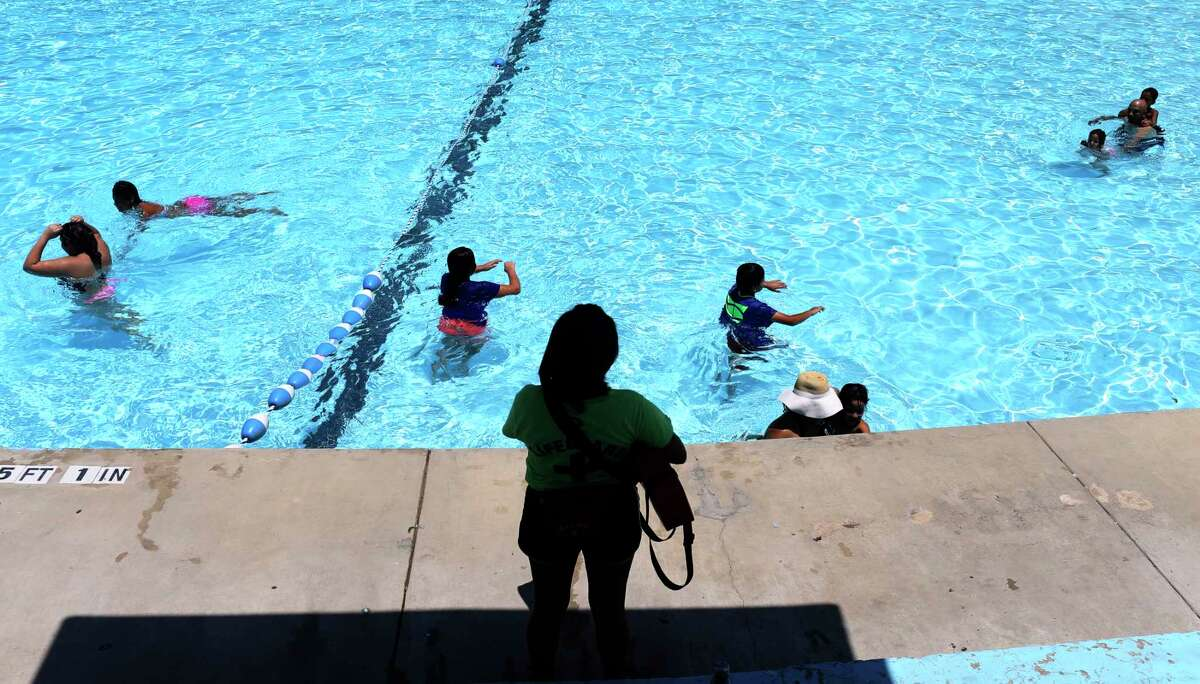 Children swimming while a lifeguard watches at one of San Antonio's public pools.