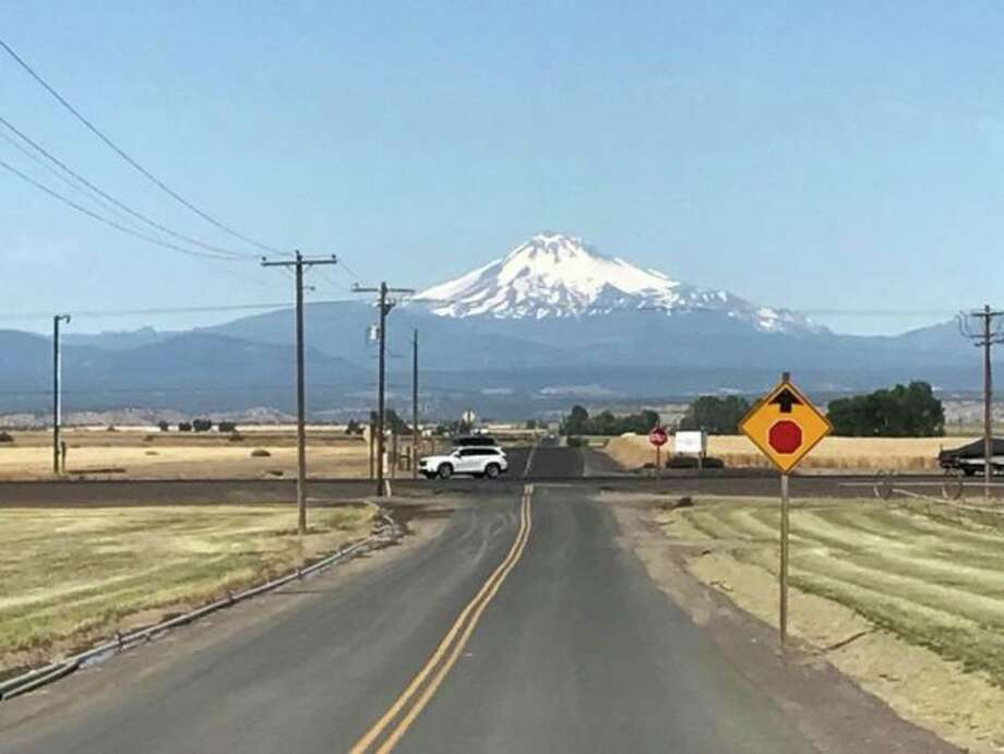 "Oregon's Mount Jefferson looms on the western horizon outside Madras. The fields on either side of the blacktop road will be turned into a ""Solartown"" campground for 4,900 tents during the runup to the Aug. 21 total solar eclipse. Photo: Alan Boyle/GeekWire"