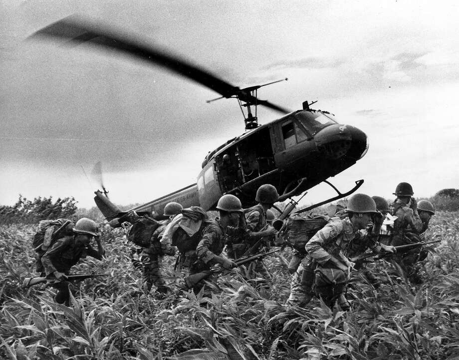 "South Vietnamese Marines rush to the point where descending a U.S. Army helicopter will pick them up. after a sweep east of the Cambodian town of Prey-Veng during the Vietnam War. It only took a second for Associated Press Photographer Huynh Cong ""Nick"" Ut to snap the iconic black-and-white image of Phan Thi Kim Phuc after a napalm attack in 1972, but it communicated the horrors of the Vietnam War in a way words could never describe, helping to end one of America's darkest eras. (AP Photo/Nick Ut, File) Photo: NICK UT, AP"