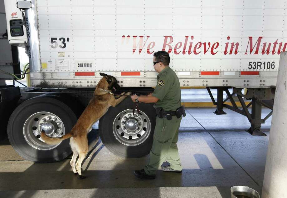 FILE - Customs and Border Patrol Agent and K9 handler officer Garza and his dog work the inspection checkpoint 27 miles outside Laredo on Tuesday, July 25, 2017. The trailer rig driven by James Matthew Bradley, Jr. that smuggled the ill-fated immigrants may or may not have passed this station. On Tuesday, traffic was heavy yet brisk at the station and agents were out in full force to inspect commercial and personal vehicles heading from Laredo to San Antonio. (Kin Man Hui/San Antonio Express-News) Photo: Kin Man Hui, Staff / San Antonio Express-News / ©2017 San Antonio Express-News