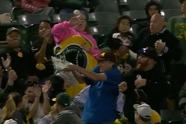 A fan attempts to catch a foul ball with his hamburger combo basket Saturday at the Oakland Athletics- Minnesota Twins game in Oakland.