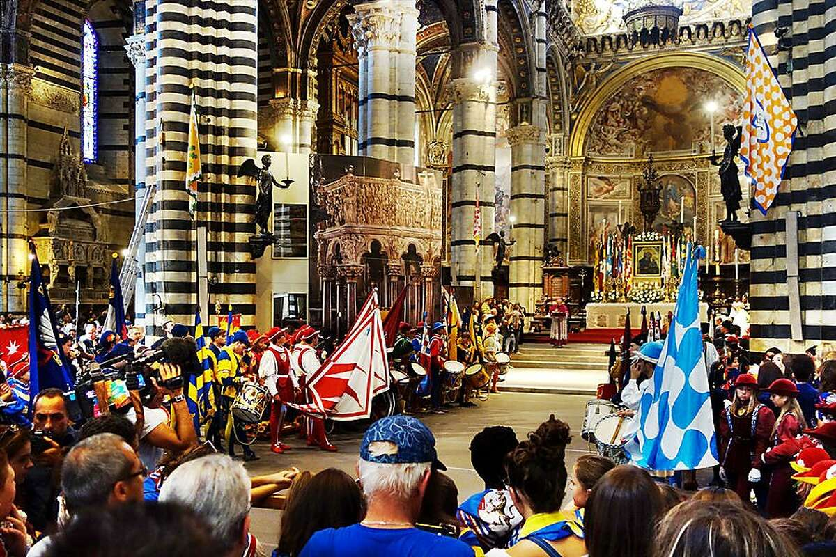 Representatives of Siena's neighborhoods, each with their own colorful costumes and banners, gather at the cathedral.