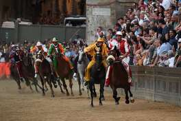 """Riders compete in the historical Italian horse race """"Palio di Siena"""" on July 2, 2017 in Siena.  / AFP PHOTO / AFP or Licensors / Claudio GiovanniniCLAUDIO GIOVANNINI/AFP/Getty Images"""