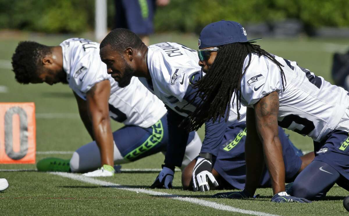 Seattle Seahawks cornerback Richard Sherman, right, stretches with strong safety Kam Chancellor, center, and free safety Earl Thomas, left, during NFL football training camp, Sunday, July 30, 2017, in Renton, Wash. (AP Photo/Ted S. Warren)