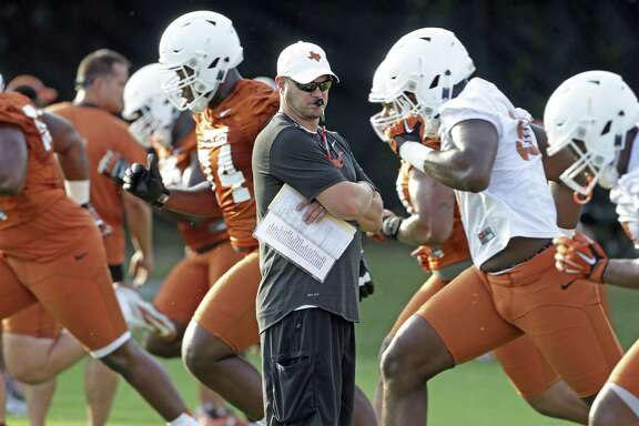 UT football coach Tom Herman watches his players warm up before practice at Denius Fields in Austin on July 31, 2017.