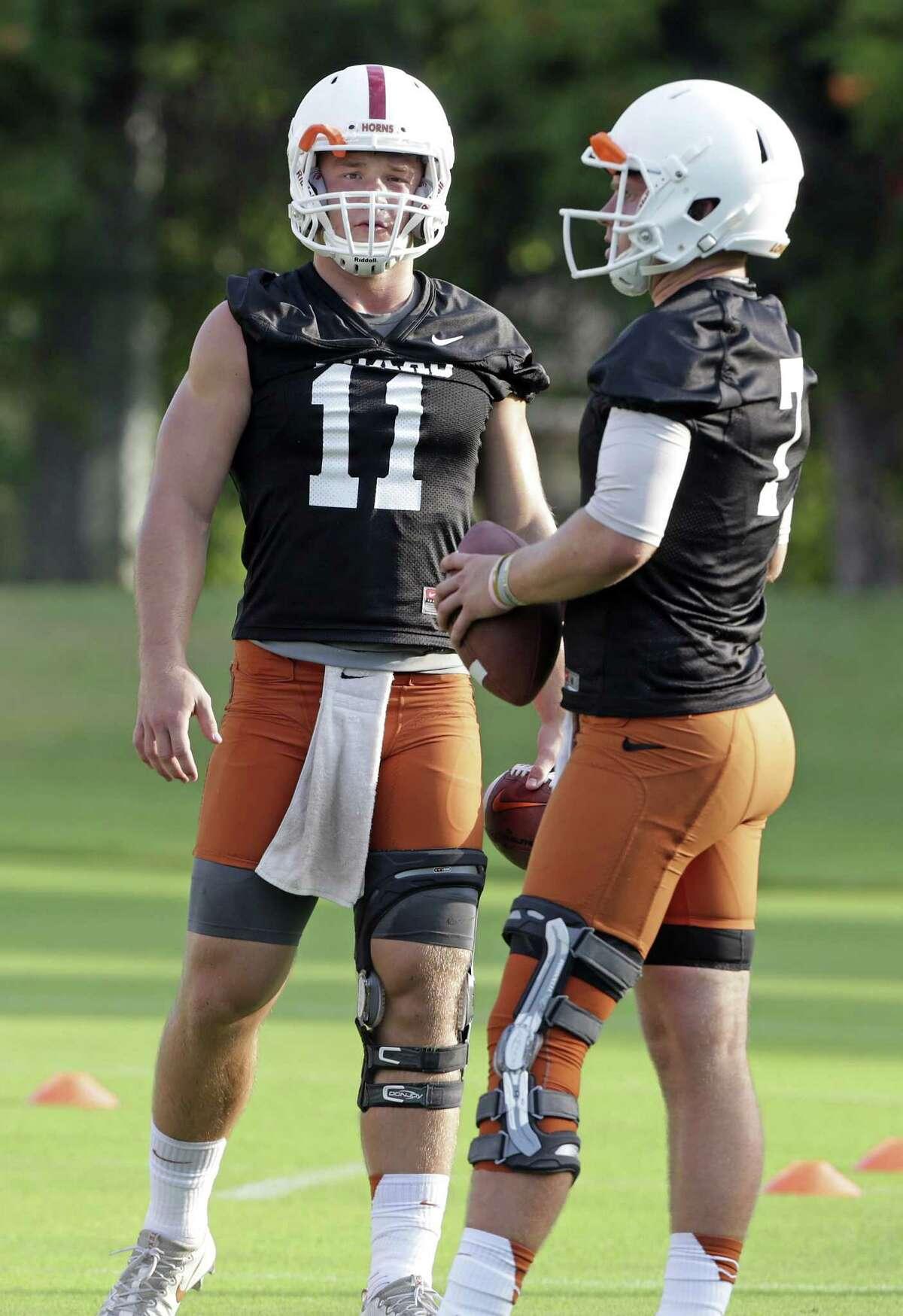 Quarterbacks Sam Ehlinger (left) and Shane Buechele hang together in drills during UT football practice at Frank Denius Fields in Austin on July 31, 2017.