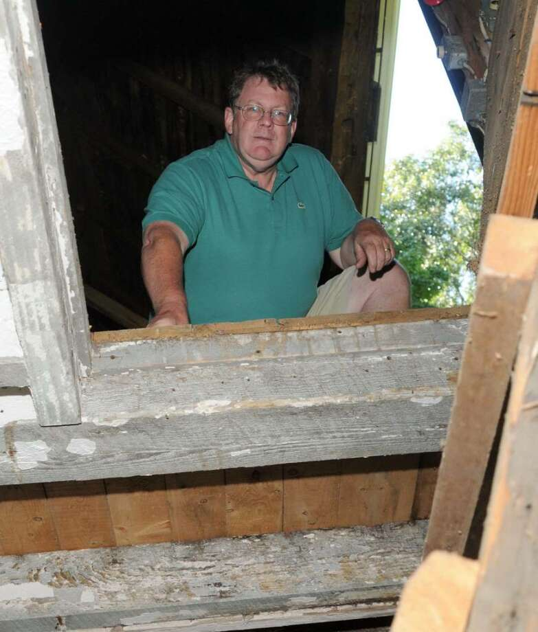 Jack Parker of New Milford, CT. on Tuesday, Sept. 1, 2009. Parker owns a barn on Old Town Park Rd., in New Milford, CT that  is believed to have hidden slaves on the Underground Railroad.  Parker looks down one of several  hatches and chutes that would have made the barn an ideal hiding place. Photo: Jay Weir / The News-Times