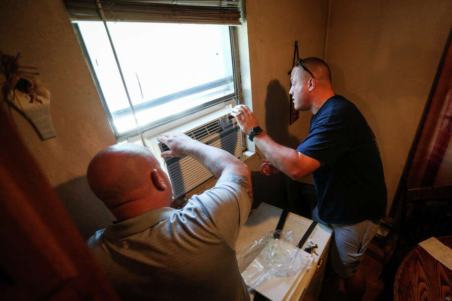 Precinct 3 Constable's deputy Dylan Jobe, right, and detective Jason Martinez, left, install a new air conditioning unit on Monday, July 31, 2017, at a home in Willis. Photo: Michael Minasi, Staff Photographer / © 2017 Houston Chronicle