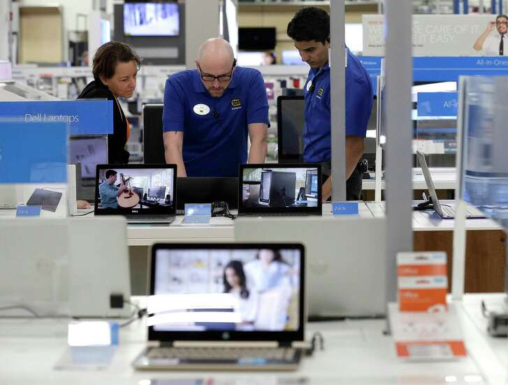 In this Tuesday, May 23, 2017, photo, employees assist a customer, at left, with a computer at Best Buy in Cary, N.C. On Friday, June 30, 2017, the Commerce Department issues its May report on consumer spending. (AP Photo/Gerry Broome)