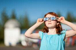Young girl with red hair watching the annular solar eclipse with special viewing glasses. Stock photo of eclipse watching
