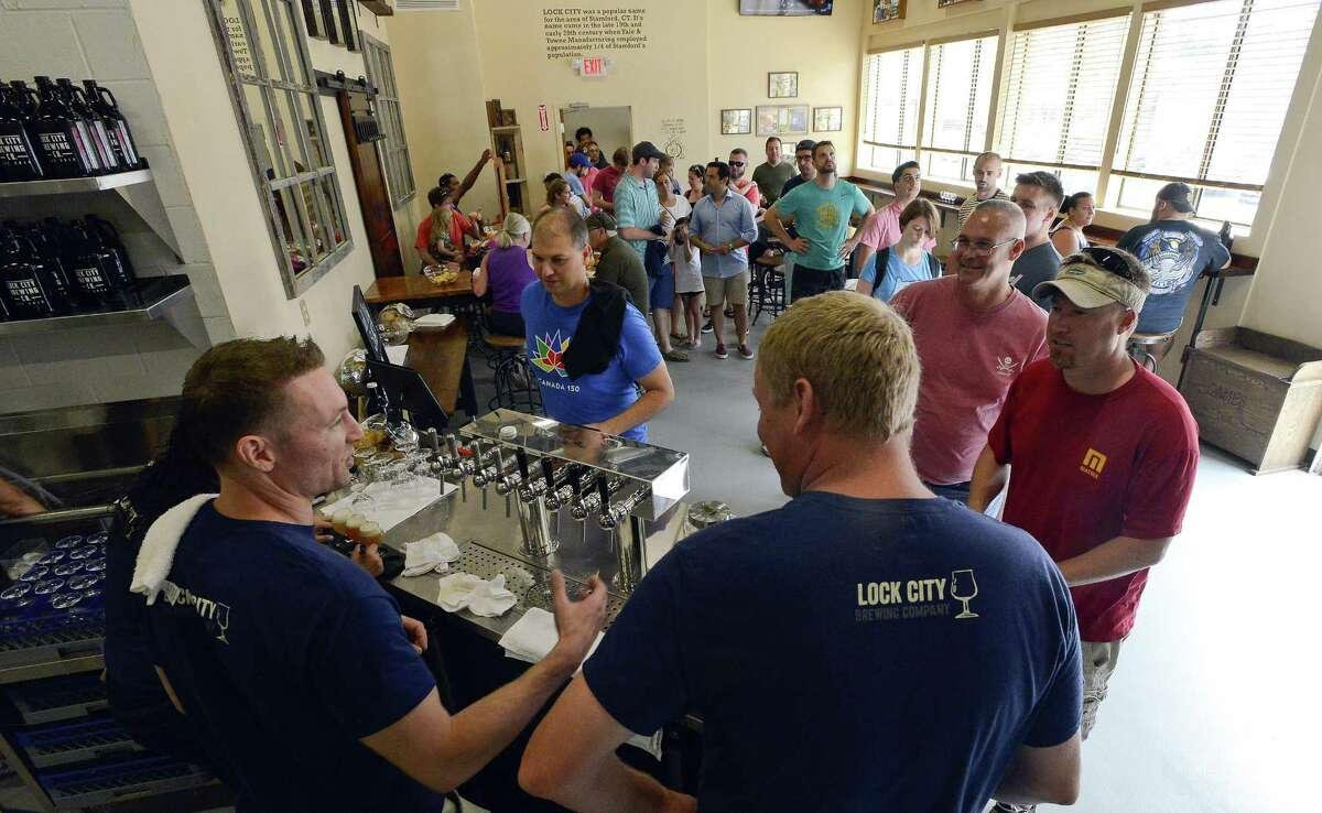 Lock City Brewing co-founders Mike Bushnell, left, and Patrick Casciolo chat with customers as the taps begin flow during the Grand Opening of their new brewery on Saturday, July 22, 2017 in Stamford, Connecticut.