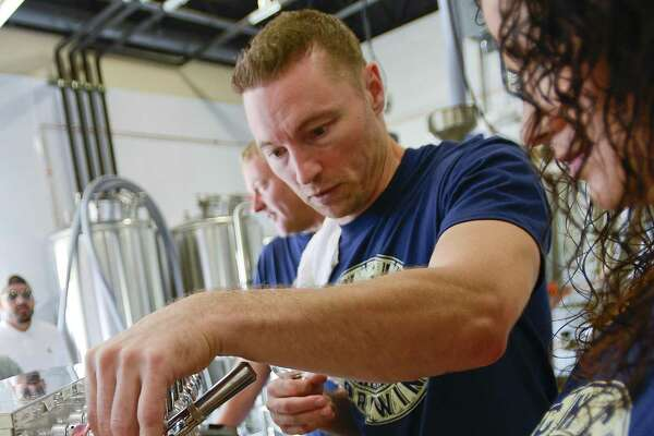 Co-founder and Head Brewer Mike Bushnell of Lock City Brewery, adjusts the flow of a tap as he helps Nikki Marcheva pour a growler of fresh ale during the Grand Opening on Saturday, July 22, 2017 in Stamford, Connecticut.