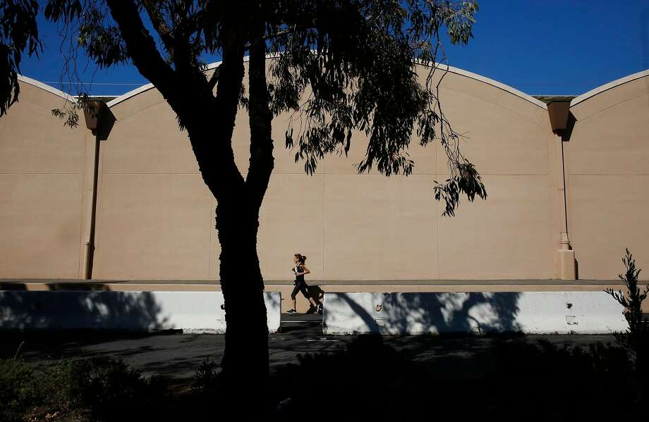 A jogger runs behind the San Francisco Bay Model visitors center building in Sausalito, which was once the Marinship warehouse. From 1942 to 1945 the World War II shipyard built 93 ships and employed more than 20,000 people. Photo: Leah Millis, The Chronicle