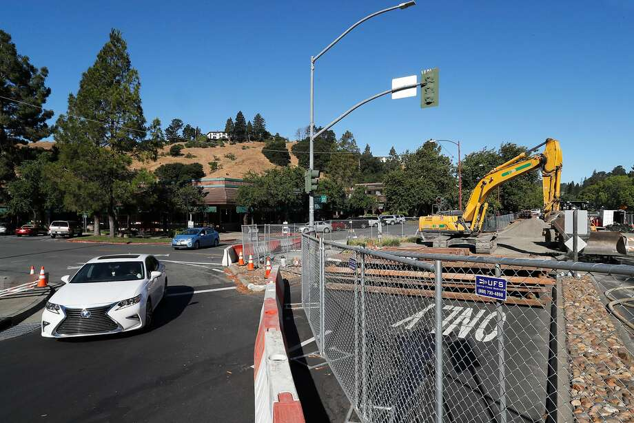 Vehicles pass by as repairs crews continue to fix the giant sinkhole at the corner of Rheem Blvd. and Moraga Rd. on Fri. July 28, 2017 in Moraga, Ca. Photo: Michael Macor, The Chronicle