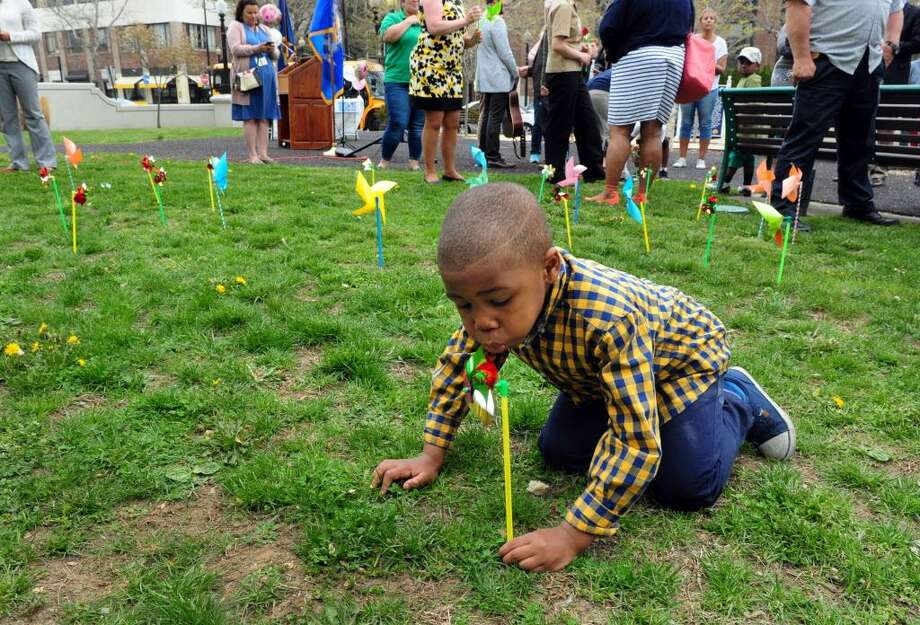Isaiah Mack, 4, blows on the pinwheel he planted during a Pinwheels for Peace event held by Action for Bridgeport Community Development (ABCD) in April 2016. Photo: Christian Abraham / Hearst Connecticut Media / Connecticut Post
