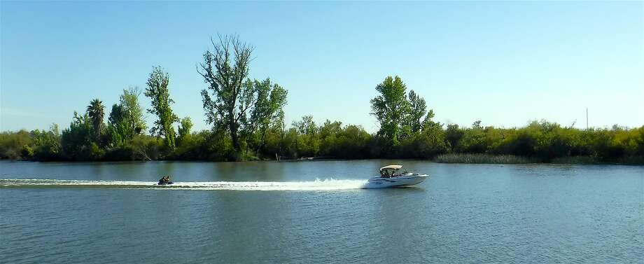 A family sport boat tows tubers on the San Joaquin River in the Delta Photo: Tom Stienstra / Tom Stienstra / The Chronicle
