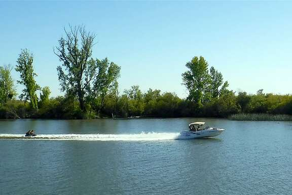 A family sport boat tows tubers on the San Joaquin River in the Delta