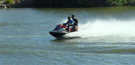 Riders on a personal watercraft jump a boat wake in the San Joaquin Delta