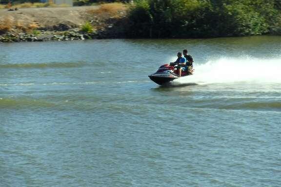 Riders on a personal watercraft jump a boat wake on the San Joaquin River near Stockton on the San Joaquin Delta