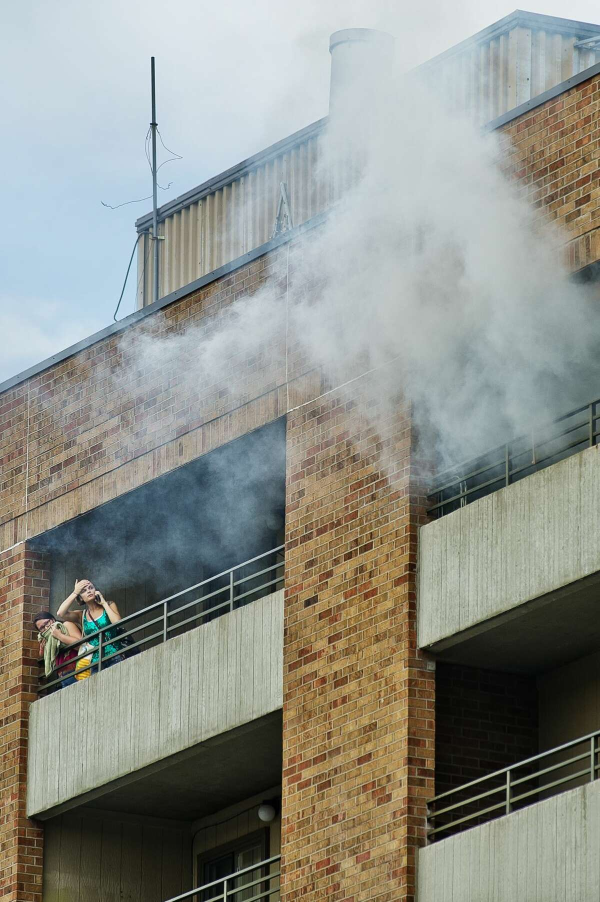 People watch from a nearby apartment as Midland firefighters battle a fire at Greenhill Apartments, 1010 Eastlawn Dr., on Monday, July 31, 2017 in Midland.