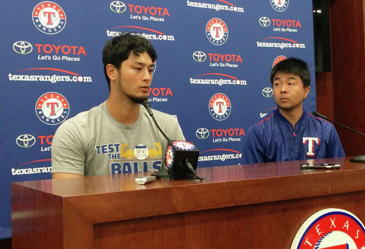 Former Texas Rangers pitcher Yu Darvish, left, responds to a question during a news conference as his translator Hideaki Sato prepares to translate regarding his trade to the Los Angeles Dodgers before a baseball game against the Seattle Mariners on Monday, July 31, 2017, in Arlington, Texas. (AP Photo/Tony Gutierrez) ORG XMIT: ARL102