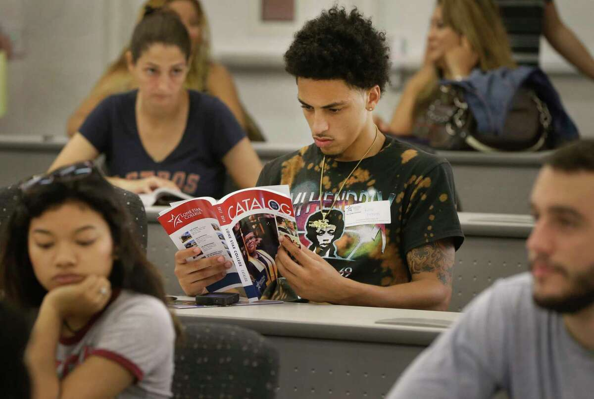 Reno Camp of Houston looks at a class catalog during a new student orientation at Lone Star.