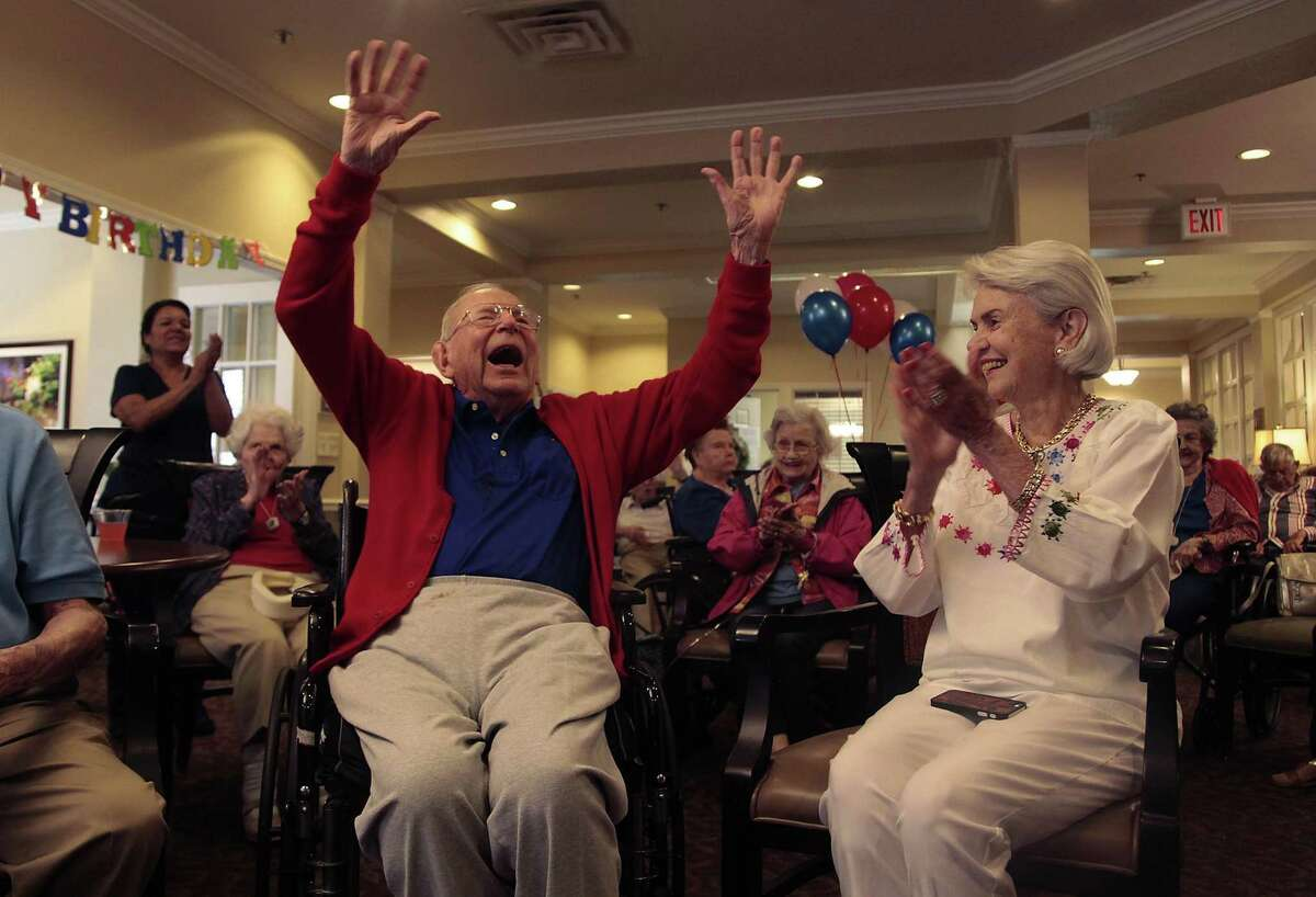 Family, friends and members of Brooksdale Alamo Heights, a local senior care center, sing