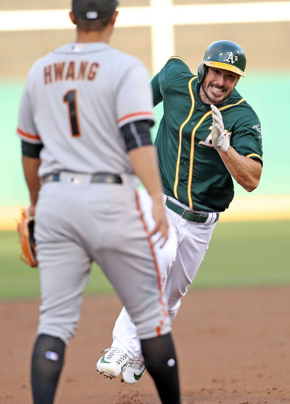 Oakland Athletics' Matt Joyce heads for third base while scoring on Jed Lowrie's RBI single in 1st inning against San Francisco Giants during MLB game at Oakland Coliseum in Oakland, Calif. on Monday, July 31, 2017.