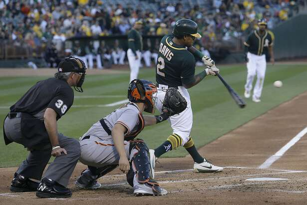 Oakland Athletics' Khris Davis (2) hits an RBI-sacrifice fly next to San Francisco Giants catcher Nick Hundley during the first inning of a baseball game in Oakland, Calif., Monday, July 31, 2017. Also pictured is umpire Paul Nauert. (AP Photo/Jeff Chiu)