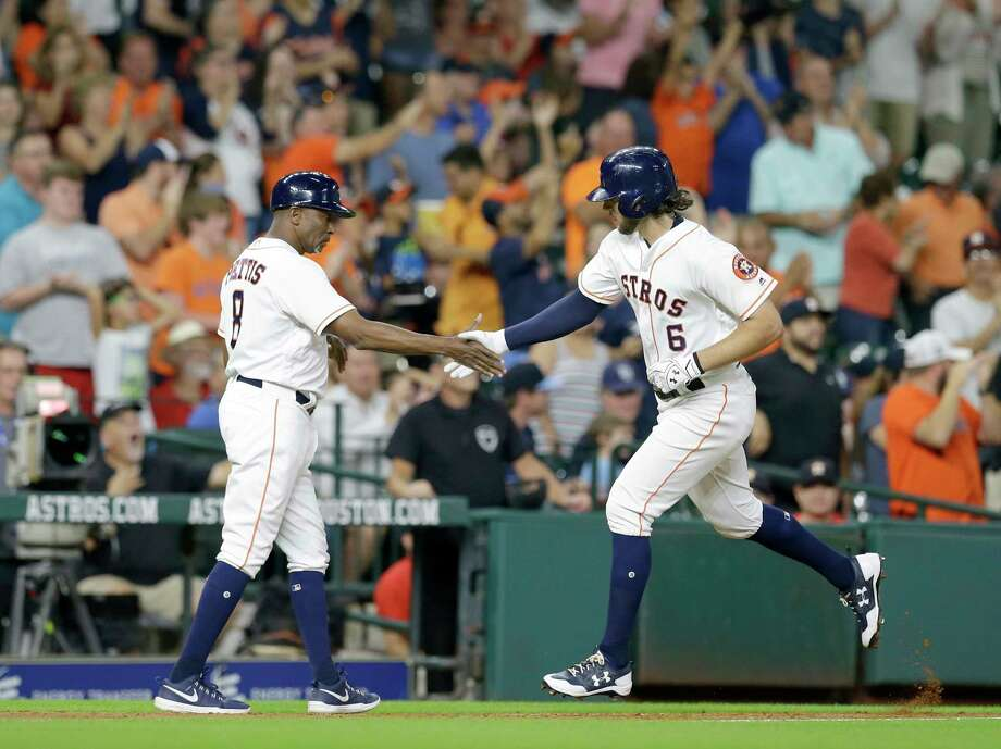 Astros outfielder Jake Marisnick, right, accepts a congratulatory handshake from third-base coach Gary Pettis after hitting a home run in the third inning. Marisnick had another in the fifth and had a total of five RBIs after doubling in the eighth. Photo: Melissa Phillip, Staff / © 2017 Houston Chronicle