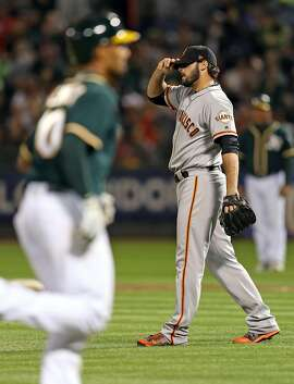 San Francisco Giants' George Kontos reacts as Oakland Athletics' Marcus Semien rounds bases after his 6th inning grand slam during MLB game at Oakland Coliseum in Oakland, Calif. on Monday, July 31, 2017.