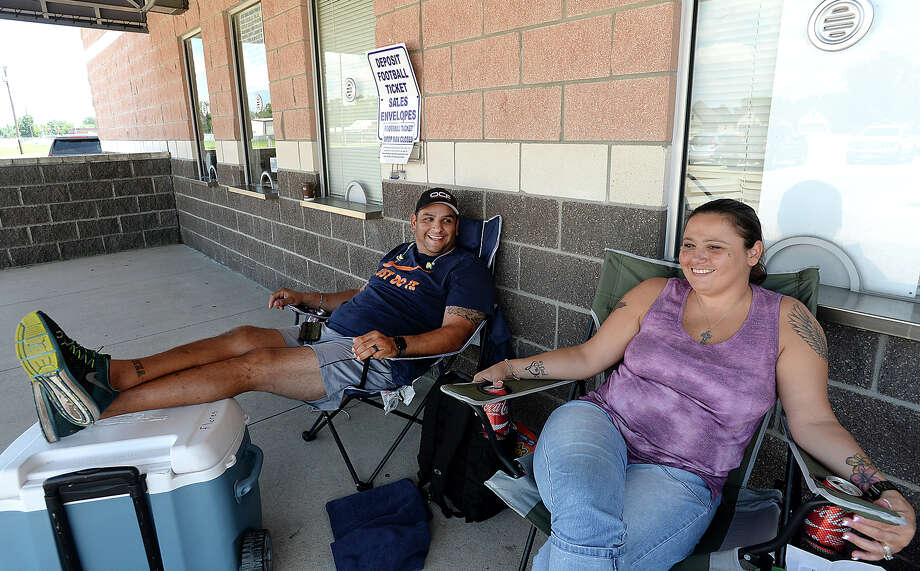 Steve Flores talks with fellow Port Neches - Groves fan and early line-goer Angie Adame as they and others line up to spend a hot Texas summer day and night at the Port Neches - Groves football stadium to purchase game tickets. Last year, Flores made his way to the window only to discover that the last ticket had just been sold. This year, he was determined to be first in line, and set out his chair, cooler, and mini generator before dawn. The ticket window officially opens Tuesday morning. Photo taken Monday, July 31, 2017 Kim Brent/The Enterprise Photo: Kim Brent / BEN