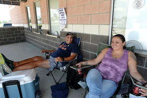 Steve Flores talks with fellow Port Neches - Groves fan and early line-goer Angie Adame as they and others line up to spend a hot Texas summer day and night at the Port Neches - Groves football stadium to purchase game tickets. Last year, Flores made his way to the window only to discover that the last ticket had just been sold. This year, he was determined to be first in line, and set out his chair, cooler, and mini generator before dawn. The ticket window officially opens Tuesday morning. Photo taken Monday, July 31, 2017 Kim Brent/The Enterprise