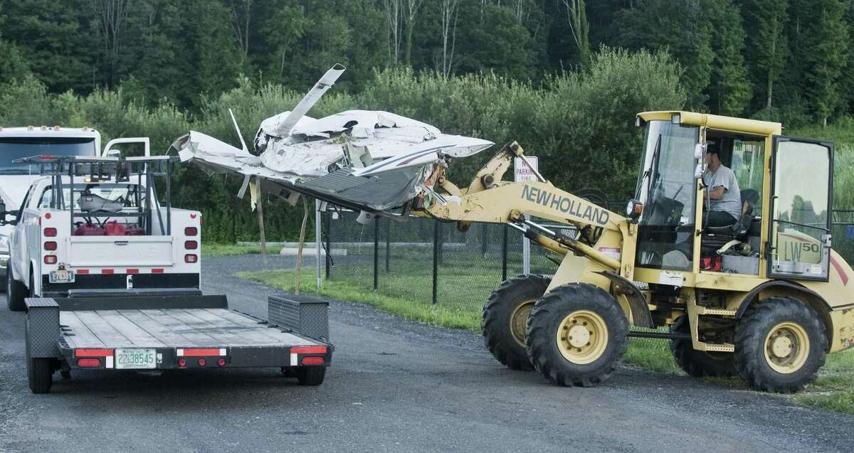 Workers lower the wing section of the plane on a flatbed at the crash site on the west side of Danbury Airport Monday.