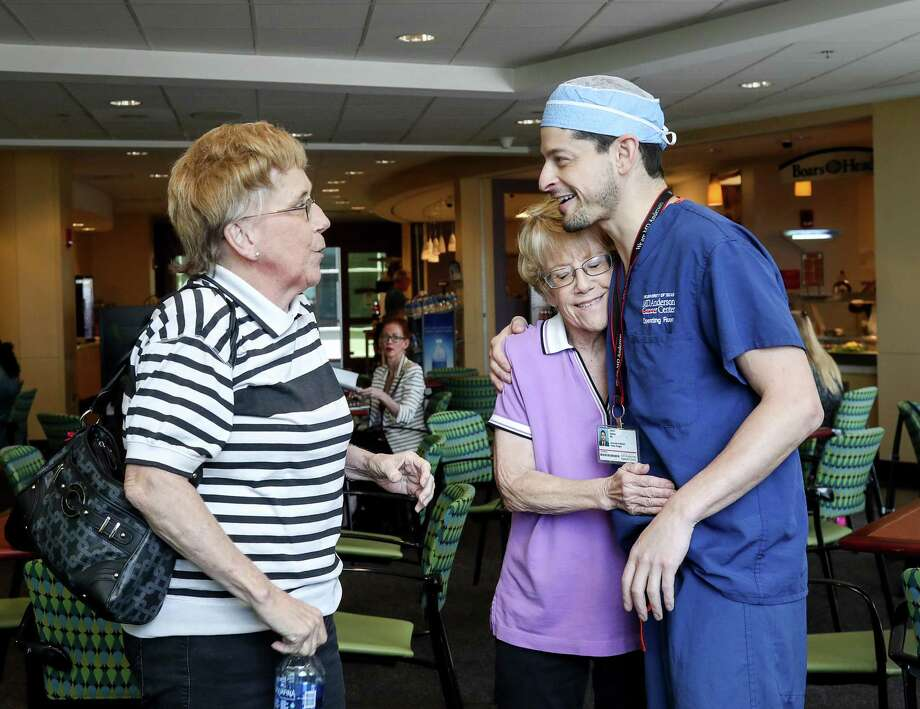 Marian Fields, center, hugs Dr. Jesse Selber, assistant professor of plastic surgery at M.D. Anderson. Her twin, Mary Jane, thanks him for treating her sister. Photo: Jon Shapley, Houston Chronicle / © 2017 Houston Chronicle